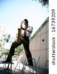 a jazz musician stands on two chairs while playing his sax during an outdoor concert - stock photo