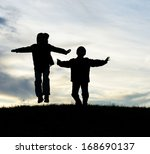 Happy children silhouettes playing in park - stock photo