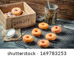 Preparing to decorate donuts with icing sugar - stock photo