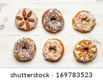 Six colorful donuts on old wooden table - stock photo