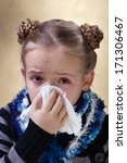Little girl with red eyes got the flu - blowing her nose using paper napkin - stock photo
