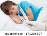 Sad child about to receive vaccine or injection - focus on syringe and phial - stock photo