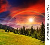 mountain steep slope with coniferous forest with rainbow in sunset - stock photo