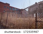 Chain link fence surrounding abandoned WWII factory - stock photo