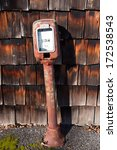 Vintage gas pump next to aged wooden shingles - stock photo