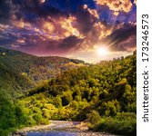 wild river flowing between green mountains on a hott summer sunset - stock photo