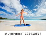 Little girl practicing surfing position at beach - stock photo