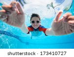 Cute little boy underwater in swimming pool - stock photo