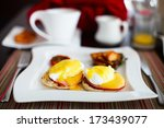 Delicious breakfast with eggs Benedict, vegetables, orange juice and coffee - stock photo
