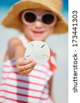 Little girl showing sand dollar she found at beach - stock photo