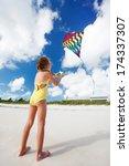 Little girl flying a kite at beach - stock photo
