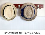 Two straw hats on a rack - stock photo