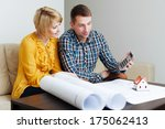 Young couple sitting on a sofa and calculating the construction budget - stock photo