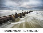 Folly Beach South Carolina Charleston SC Seascape landscape photography featuring moving ocean water against an old wooden erosion control breakwater - stock photo