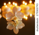 orchid with reflection and burning candles in the background - stock photo