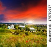 red poppy flowers in the grass and the monastery and church of green at sunset - stock photo