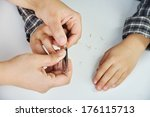 Mother cutting son's nails using the clippers - stock photo