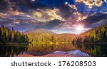 view on lake near the pine forest on mountain background at sunset - stock photo