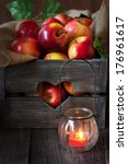 Sweet ripe red apples in an old wooden box and garden jar candle on wooden background.  - stock photo