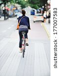 Woman on bike in green summer city - stock photo