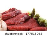 fresh raw beef meat steak fillet on wooden plate with asparagus and tomatoes ready to prepare isolated over white background - stock photo