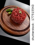 very big raw hamburger cutlet with sprouts and chili pepper on wooden plate over black background - stock photo