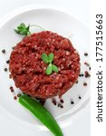 very big raw hamburger cutlet with sprouts and chili pepper on white plate isolated over white background - stock photo
