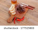 fresh beef meat steak with red hot pepper and bun slices served on plate with whiskey on wood over table with cutlery - stock photo