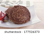 fresh juicy beef meat hamburger with dry pepper on white plate over tablecloth with cutlery - stock photo