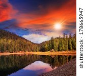 view on lake near the pine forest late in evening on mountain background at sunset - stock photo