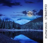 view on lake near the pine forest late midnight on mountain background in moon light - stock photo