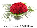 A bouquet of red roses in a transparent glass vase. The isolated image on a white background. - stock photo