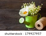 Spring flowers in watering can on wooden background. - stock photo