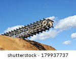 Reclaimer Boom with Scraper Chains and Flights reclaiming material in a Paper Mill  - stock photo