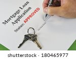 Hand Signing An Approved Real Estate Mortgage Loan Document With House Keys - stock photo