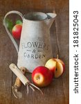 Red ripe apples and gardening tools  on a wooden board in the orchard. Textured photo. Vintage style. - stock photo