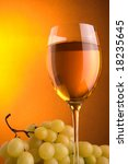 a glass  with white wine and green grape - stock photo