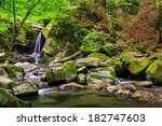 incredibly beautiful and clean little waterfall with several cascades over large stones in the forest comes out of a huge rock covered with moss - stock photo