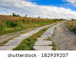 road of concrete slabs through the field turns uphill to the sky - stock photo