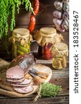 Rural smokehouse with ham and herbs - stock photo