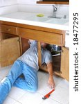 Man Under Kitchen Sink Reaching for Pipe Wrench. Do-it-yourself home repair project concept. - stock photo