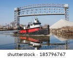 A red, black, and white tugboat makes it's way past a raised drawbridge and a mound of aggregate material as it heads for the open waters of Lake Erie from the Cuyahoga River in Cleveland, Ohio - stock photo