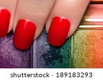 Closeup of fingers with red nails and colorful eyeshadow palette. Manicure and makeup concept - stock photo