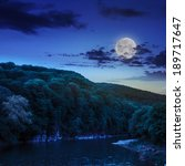 calm river flowing between green mountains on a dark summer night in moon light - stock photo