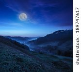 cold morning fog on a hillside meadow near mountain village at night in moon light - stock photo