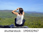 A woman hiker on an overlook looking for birds. - stock photo