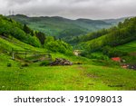 mountain summer landscape. trees and fence near meadow on hillside under  sky with clouds - stock photo