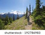 Young man enjoying the stunning scenic view of mountain Rainer on hiking trail. Washington, Seattle - stock photo