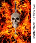 A medieval broadsword thrust through the top of a human skull surrounded by flames - stock photo