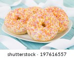 Doughnuts - Ring doughnuts topped with cake frosting and colorful sprinkles on a blue background. - stock photo